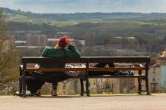 El sentarse joven de los pares relajado en un banco Imagenes de archivo