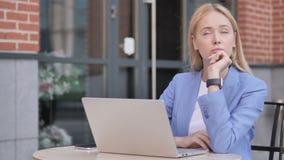 El sentarse joven de pensamiento de la empresaria al aire libre almacen de video