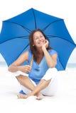 Playa azul del paraguas de la mujer madura feliz Fotografía de archivo