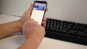 El sentarse masculino en de escritorio y el practicar surf en su móvil Fondos de la tecnolog?a Uppsala suecia almacen de metraje de vídeo