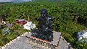 El sentarse meditando al monje negro Statue en templo budista Provincia de Phang Nga, Tailandia Antena de HD almacen de metraje de vídeo