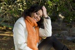 El sentarse modelo femenino sonriente feliz afuera Imágenes de archivo libres de regalías