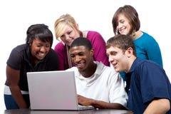 El sentarse multirracial de los estudiantes universitarios un ordenador Fotos de archivo libres de regalías