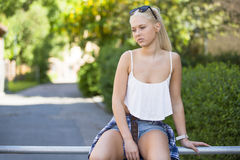 El sentarse pensativo y triste de la chica joven al aire libre Fotos de archivo libres de regalías
