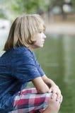 El sentarse por el agua Foto de archivo