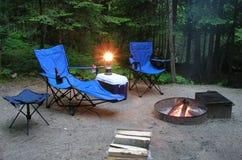 El sentarse por el fuego en un sitio para acampar Imagen de archivo libre de regalías