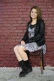 El sentarse por una pared de ladrillo pintada Fotografía de archivo