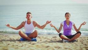 El sentarse practicante de las actitudes de la yoga de la gente metrajes