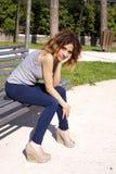 El sentarse que espera de la muchacha en un banco en un parque Fotos de archivo libres de regalías