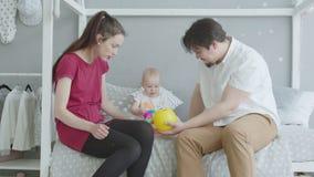 El sentarse que juega infantil alegre en cama con los padres almacen de metraje de vídeo