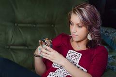 El sentarse que manda un SMS de la muchacha en recliner Imagenes de archivo