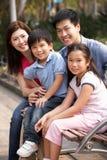 El sentarse que recorre de la familia china en banco en parque Imagen de archivo