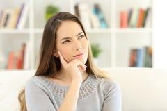 El sentarse que se pregunta de la mujer en casa Fotografía de archivo libre de regalías
