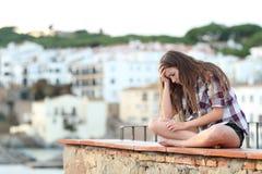 El sentarse que se queja adolescente triste en una repisa de vacaciones fotos de archivo