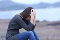 El sentarse que se queja de la mujer triste en la playa fotos de archivo libres de regalías