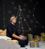 El sentarse que se sienta de la mujer en las almohadas con los regalos está bebiendo té caliente imagenes de archivo