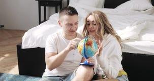 El sentarse querido al lado de la cama está mirando el globo que elige un lugar para viajar en luna de miel Concepto de la relaci metrajes