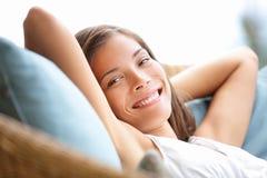 El sentarse relajante de la mujer cómodo en sofá Fotos de archivo