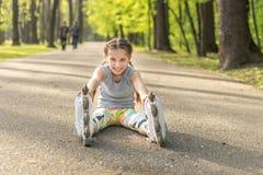 El sentarse rollerblading de la muchacha en el asfalto, estirando Foto de archivo libre de regalías
