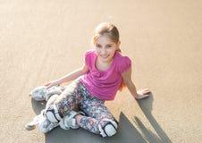 El sentarse rollerblading de la muchacha en el asfalto, estirando Imagenes de archivo