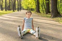 El sentarse rollerblading de la muchacha en el asfalto, estirando Foto de archivo