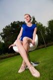 El sentarse rubio de la muchacha al aire libre en una silla de eslabón giratorio Imagenes de archivo