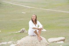 El sentarse solo pensativo de la mujer al aire libre Imagen de archivo libre de regalías