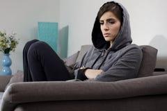 El sentarse solo y corazón roto de la sensación de la mujer en casa en el sofá Imagenes de archivo