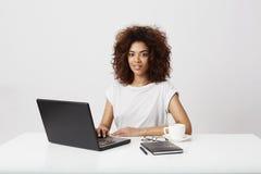 El sentarse sonriente de la empresaria africana en la tabla en el lugar de trabajo sobre el fondo blanco Fotos de archivo libres de regalías