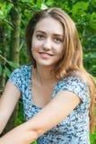 El sentarse sonriente de la muchacha adolescente en el parque y mirada de la cámara Fotos de archivo