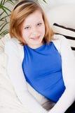 El sentarse sonriente de la muchacha feliz del adolescente en el sofá Fotos de archivo libres de regalías