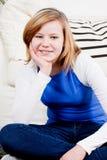 El sentarse sonriente de la muchacha feliz del adolescente en el sofá Imágenes de archivo libres de regalías