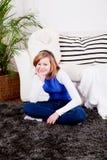 El sentarse sonriente de la muchacha feliz del adolescente en el sofá Fotografía de archivo