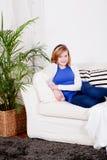 El sentarse sonriente de la muchacha feliz del adolescente en el sofá Imagen de archivo libre de regalías
