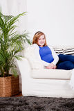 El sentarse sonriente de la muchacha feliz del adolescente en el sofá Imagenes de archivo