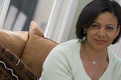 El sentarse sonriente de la mujer afroamericana confiada en el sofá Foto de archivo libre de regalías