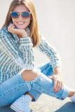 El sentarse sonriente de la mujer alegre en el camino Imágenes de archivo libres de regalías
