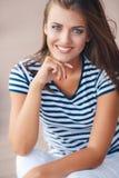 El sentarse sonriente de la mujer alegre en el camino Imagen de archivo libre de regalías