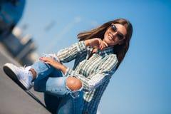 El sentarse sonriente de la mujer alegre en el camino Fotos de archivo
