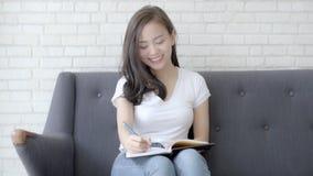 El sentarse sonriente de la mujer asiática hermosa en estudio del sofá y aprendizaje escribiendo el cuaderno en casa