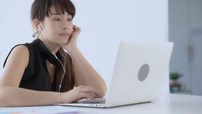 El sentarse sonriente de la mujer asiática joven hermosa usando música que escucha del ordenador portátil con el auricular para a
