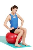 El sentarse sonriente de la mujer triguena en bola del ejercicio Imagen de archivo