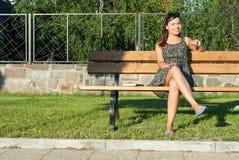 El sentarse sonriente de la señora bonita en banco en parque Imagen de archivo libre de regalías