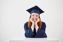 El sentarse sonriente de sueño de pensamiento graduado de la muchacha soñadora feliz sobre el fondo blanco Foto de archivo