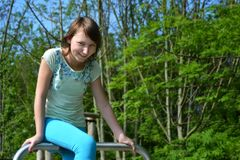 El sentarse sonriente del adolescente feliz en un tubo del metal en el parque Imagen de archivo libre de regalías