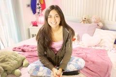 El sentarse sonriente del adolescente hispánico lindo en cama Foto de archivo libre de regalías