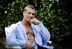 El sentarse sonriente del hombre joven hermoso del músculo, al aire libre, con la camisa abierta Foto de archivo libre de regalías