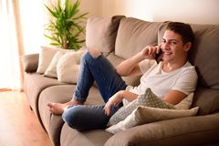 El sentarse sonriente del muchacho joven en el sofá que habla en el teléfono Foto de archivo