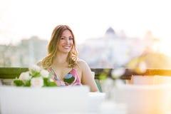El sentarse sonriente hermoso y encantador de la mujer al aire libre imagenes de archivo