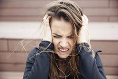 El sentarse triste enojado de la mujer joven al aire libre fotografía de archivo